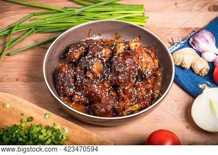 Ready Pork Ribs Stewed In Sweet And Sour Sauce In A Plate On The Table With Ingredients For Cooking,