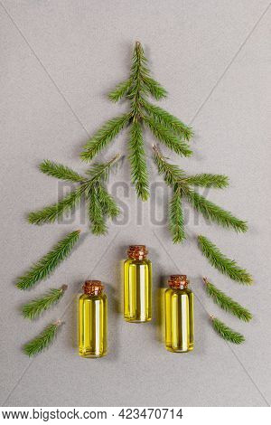 Green Spruce Twigs And Small Glass Bottles Of Essential Fir Oil Laid Out As Christmas Tree On Grey T