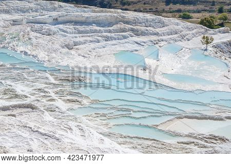 Panorama Of Travertine Pools Filled With Blue Water. Rock Structures Formed By Water Containing Carb