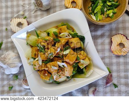 A Dish Made Of Pak Choi, Tofu, And Spring Onion Served In The White Plate. There Are Slices Of Dried
