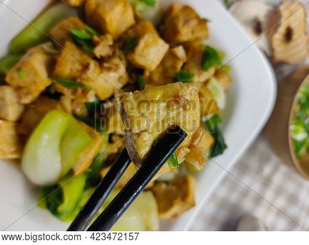 Piece Of Tofu Held With Chopsticks Above The Dish Made Of Pak Choi, Tofu, And Spring Onion. The Dish