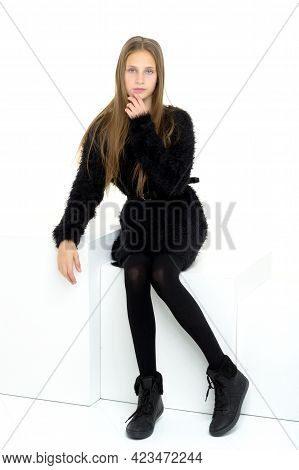Pretty Teenage Girl Sitting On White Cube In Studio. Beautiful Stylish Long Haired Girl Wearing Blac