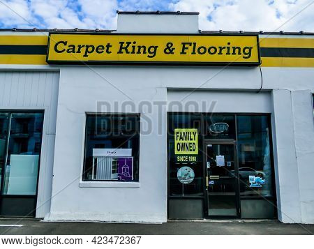 NORWALK, CT, USA - JUNE 11, 2021:  Carpet King and Flooring  building facade with blue sky and puffy clouds view from walkway Post Road