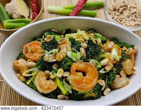 Detail Of Dish Made Of Broccoli, Shrimp, Peanuts, And Onion Served In A White Oval Bowl. As A Decora