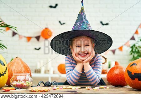 Happy Halloween! A Little Girl In A Witch Costume For Halloween Is Sitting At A Table With Sweets An