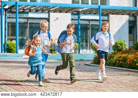 Group Of School Children With Backpacks Run Out Of School, After The End Of Classes. Classmates, Sch