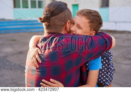 Happy Family Of Father And Son. A Man Hugs His Child, A Primary School Student. Dad Meets The Boy Af