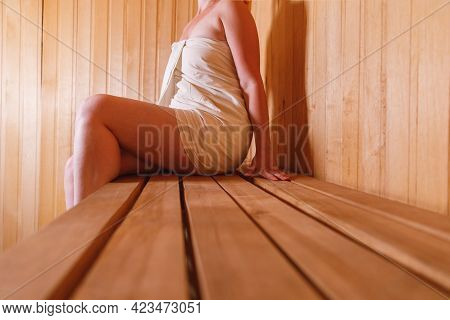 Traditional Old Russian Bathhouse Spa Concept. Woman In Towel Relaxing In Traditional Finnish Sauna