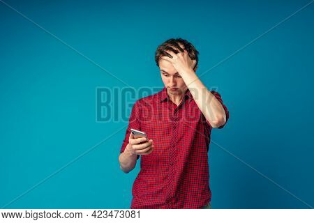 Scared Young Guy Holding A Smartphone In His Hand Covers His Face With His Hand In Shock At The Erro