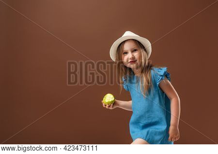 Portrait Of A Funny Cheerful Little Girl Holding An Apple On A Brown Background. The Child Is Wearin