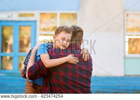 Happy Family Father And Son. Man Hugs His Child, Primary School Student. Dad Meets Schoolboy After S