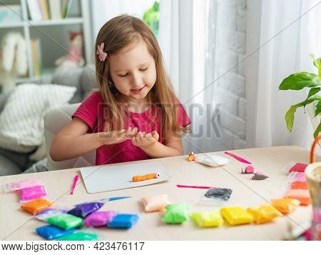 Charming Cute Little Baby Girl With Soft Colorful Clay. A Healthy Child Plays And Creates Toys From