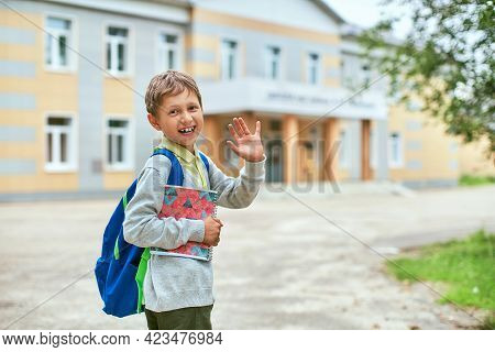 Back To School. A Boy From An Elementary School In The Schoolyard Waves. A Schoolboy In Glasses With