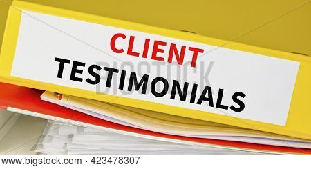Client Testimonials Text On Binder Stacked Over In An Office. Business And Marketing Concept.