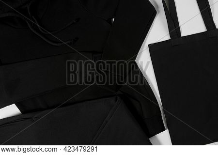 Dark Clothes Lying On A White. Black Stylish Bag On Isolated Background. Style And Beauty. Jeans Lyi