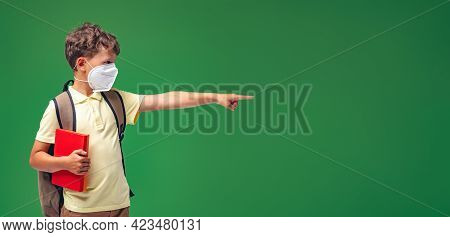 Mischievous Schoolboy In Protective Mask Standing Against Green Board. Excited Child Points Finger T