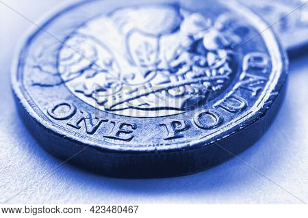 1 One British Pound Coin Close-up. Light Blue Background On An Economy, Business, Financial Or Banki