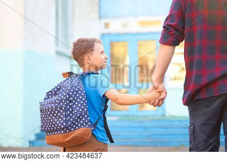 Dad Walks The Child To School. He Encourages The Student To Accompany Him To School. A Caring Father