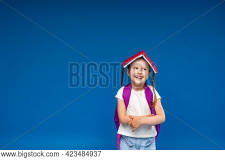 Happy Smiling Little Girl Is Having Fun On A Blue Background With A Book On Her Head. A School Girl