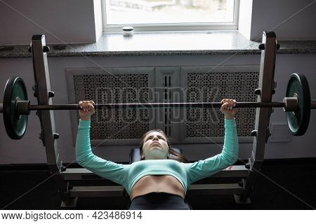 A Young Athletic Woman Does A Bench Press. Athletic Strong Woman. The Concept Of Sports And Strength