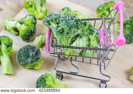 Frozen Broccoli In The Shopping Cart On Light Wooden Background. Vegetable Preservation And Grocery