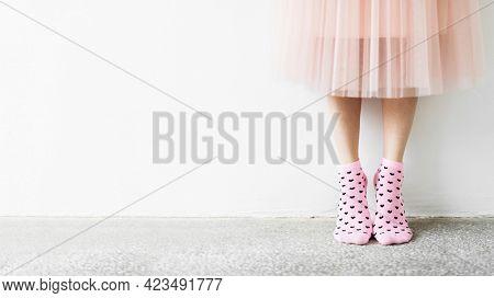 Woman in a skirt wearing pink socks wallpaper