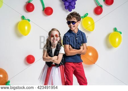 Cool Very Stylish Children In Sunglasses And Fashionable Clothes, Posing At Background Fruit Balls.