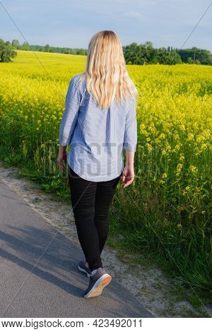Back View Of A Girl In A Blue Shirt Against The Background Of A Blooming Rapeseed Field. Bright Yell