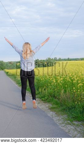 Rear View Of A Happy Girl Jumping Against The Background Of A Blooming Rapeseed Field. Bright Yellow