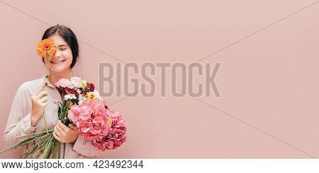 Beautiful young girl with an orange gerbera flower