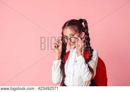 Happy Little Girl In Glasses And Uniform With Large Backpack Is Having Fun At School. Child Adjusts
