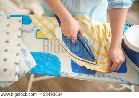 Close-up, Top View, A Woman Ironing Clothes With An Iron On An Ironing Board After Washing On A Sunn