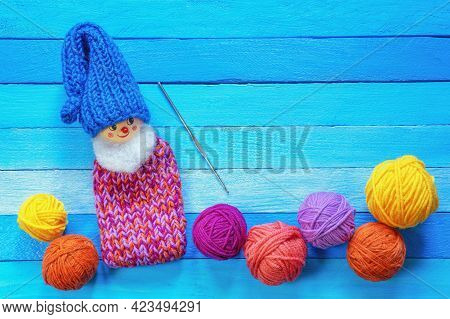 Hobby And Knitting Concepts.  Multi-colored Balls Of Wool On Blue Rustic Table. Funny Knitted Gnome