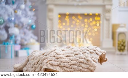 Christmas Light Background. Decorated With Christmas Decor. Wicker Basket With Knitted Blanket Sits