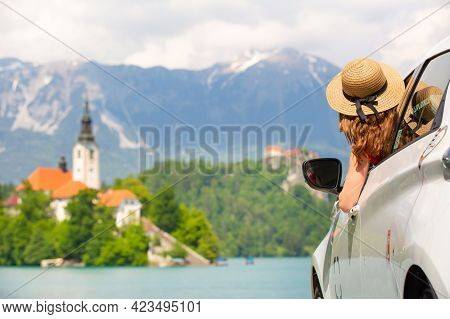 Happy Young Woman On Vacation Leaning Out Of Car Window On Shore Of Bled Lake, Country Of Slovenia.
