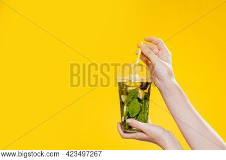 Young Woman Hand Holding A Glass Of Cocktail With Mint. Studio Photo With Yellow Background