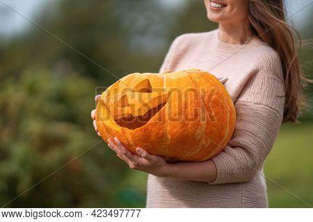 Happy Woman Holds Pumpkin Lantern Or Pumpkin In Garden During Halloween Celebration. Carved Pumpkins