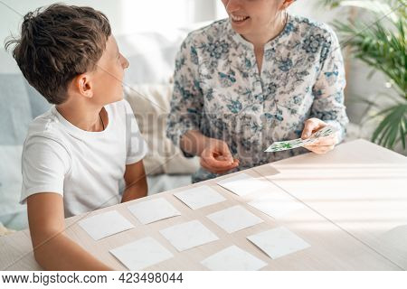 7-year-old Boy Plays A Memory Board Game With His Mother To Develop Memory And Attention At Home. Th