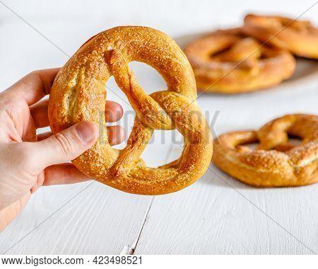 Hand Holding A Freshly Baked Pretzel. Homemade Soft Pretzels Closeup
