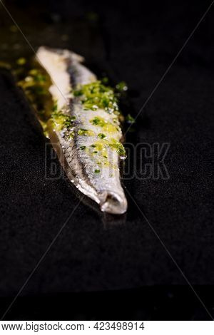 Piece Of Anchovies With Garlic, Parsley And Oil On A Black Background.