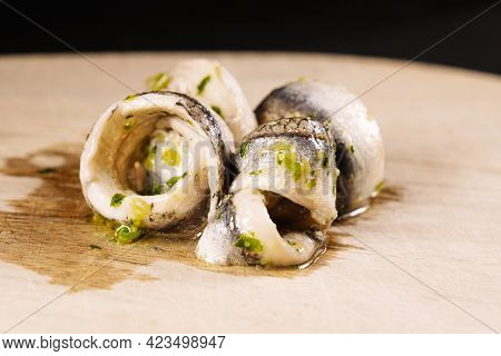 Piece Of Anchovy With Garlic, Parsley And Oil On A Chopping Wood.
