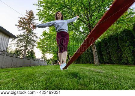 Adventurous White Caucasian Adult Woman Walking On A Slackline Between Trees In A Neighborhood Park.