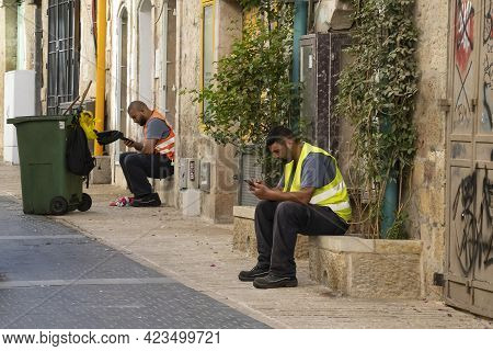 Jerusalem, Israel - June 3rd, 2021: Two City Street Cleaners Taking A Break From Work To Use Their C