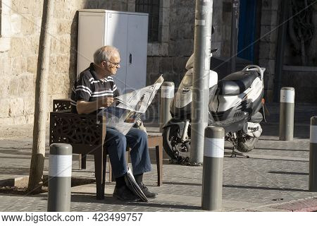 Jerusalem, Israel - June 3rd, 2021: An Elderly Man Reading The Daily Newspaper On A Bench In A Jerus