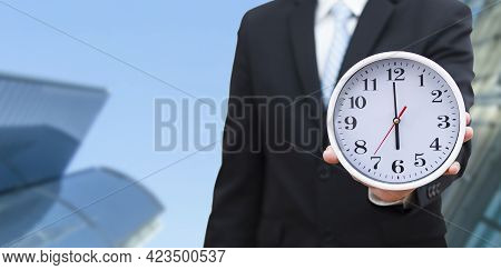 Concept Of Saving Time, Businessman Holding A Clock Against Time 6 Am In The Morning On The White Ba