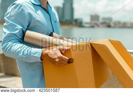 Unemployed Businessman Is Carrying A Brown Cardboard Box. Unemployed And Economy Concept.