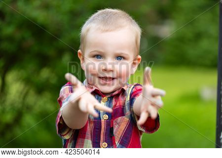 A Child Boy Holding Out His Hands. He Is Standing Outdoors In A Park. Boy Is Looking Happy.