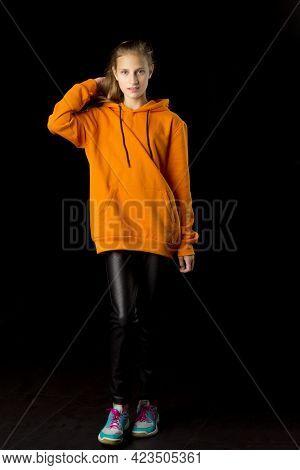 Full Length Shot Of Stylish Teenage Girl. Joyful Girl With Ponytail Wearing Oversized Orange Hoodie