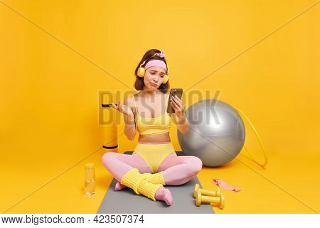 Hesitant Asian Woman Looks With Clueless Expression At Smartphone Display Takes Break After Aerobics