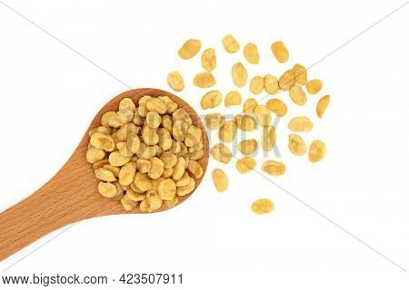 Roasted fava beans for a healthy vegan diet snack food in a wooden spoon and loose on white background. High in protein, vitamins, dietary fibre and  nutrients. Flat lay, top view.